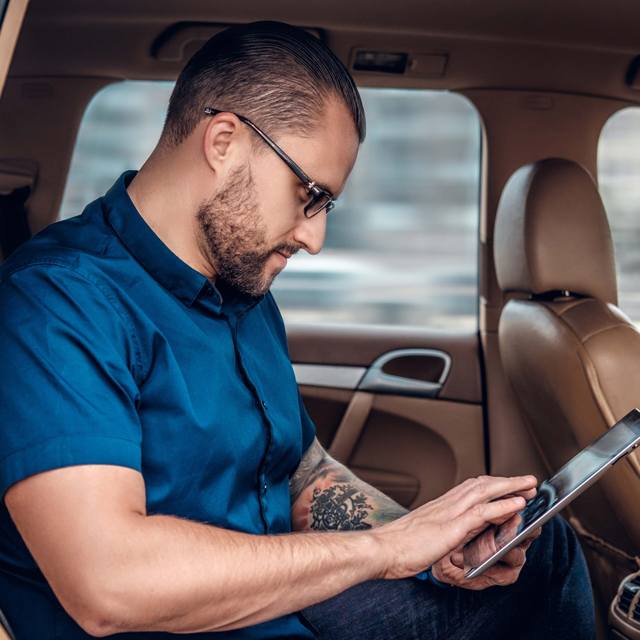 Man With Tablet Sitting In The Back Sit Of A Car