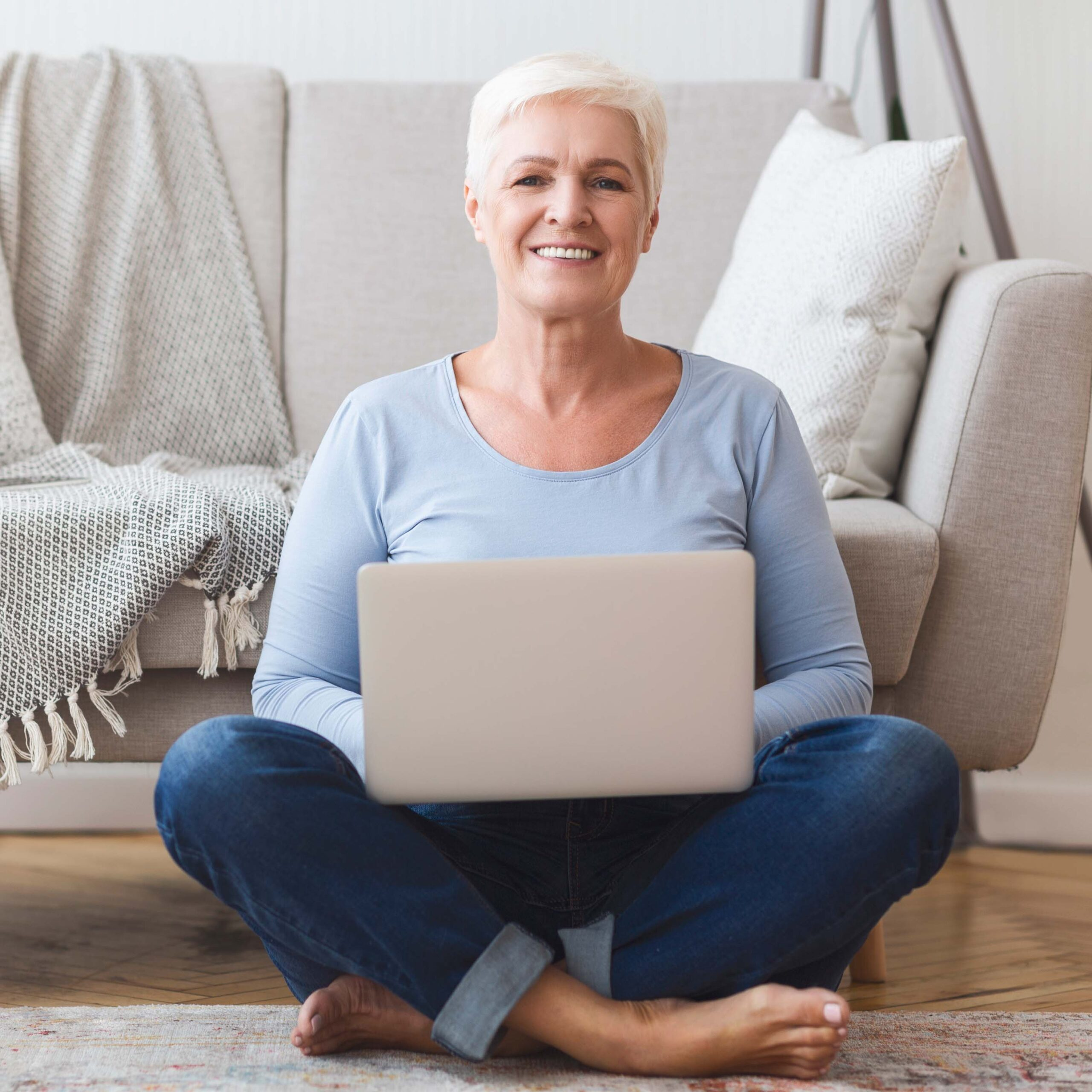 Senior Woman Sitting In The Floor With A Laptop On Her Lap And A Sofa In The Back