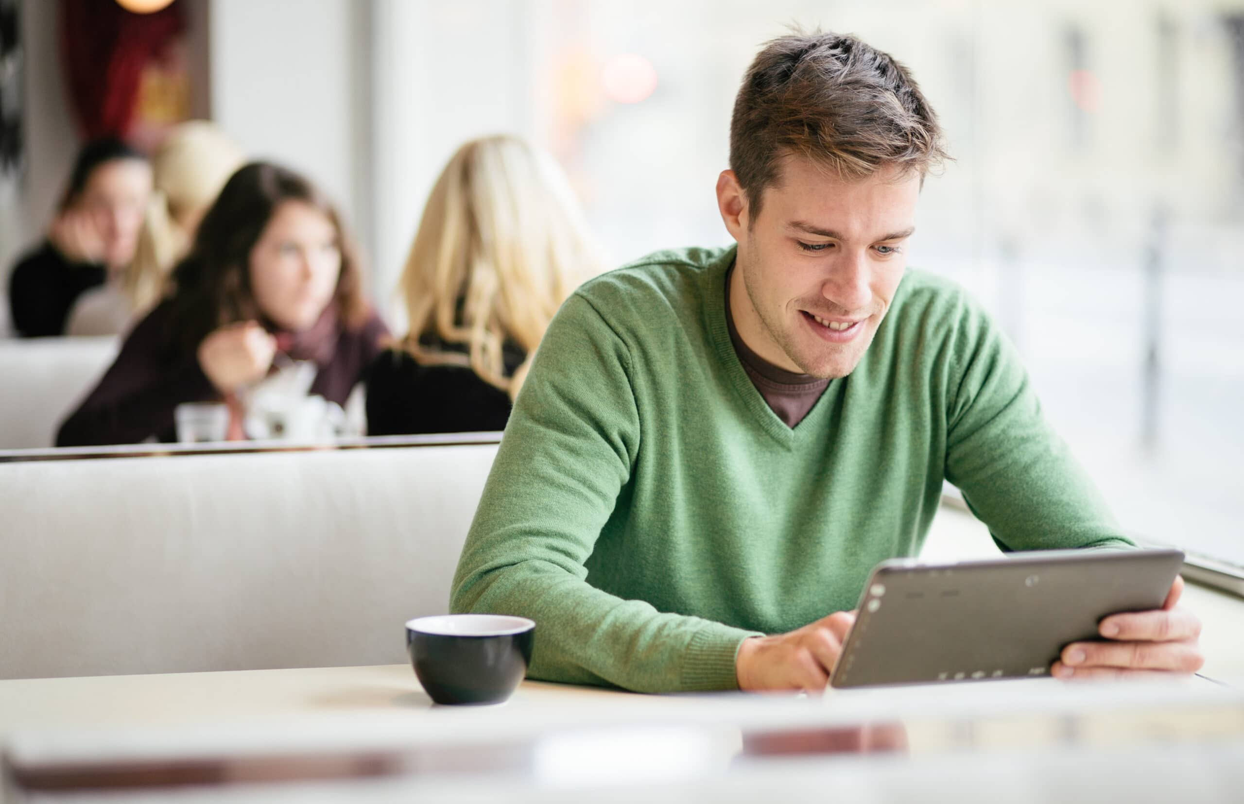 A Man Sitting In A Coffee Shop Working In A Tablet