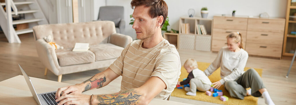 Man With Tattoos Working In A Laptop At A Living Room With A Woman Playing With A Baby In The Back
