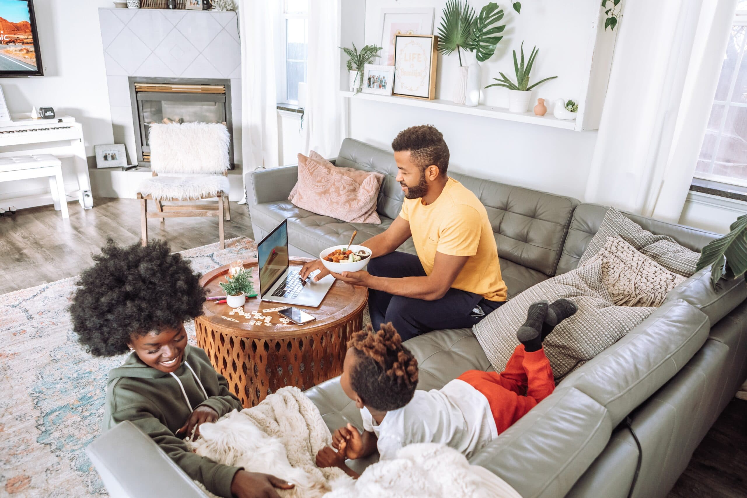 A Man Working In A Laptop Sitting At A Living Room With A Smiling Woman And A Little Boy